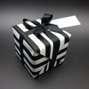 Papier cadeau noir et blanc, rayures. Présentation en paquet.