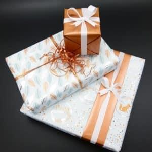 Papiers cadeaux blanc et cuivre, parfait pour les fêtes de Noël.